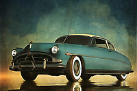 The iconic Hudson Hornet is more than a classic. It is a legendary vehicle that harkens back to a glory era of the American auto. The car got some renewed interest when it was one of the featured characters in the animated Pixar film Cars (and was voiced by another American legend by the name of Paul Newman). This is a compelling scene in which an immovable object stands firmly against the elements. Some might even call it inspiring. Available as wall art, t-shirts, or interior d&eacute;cor products, this is an ideal piece for those who appreciate the greats.<br /> <br /> About the car: The Hudson Hornet is an automobile which was produced by the Hudson Motor Car Company of Detroit, Michigan, between 1951 and 1954 and then by American Motors Corporation (AMC) in Kenosha, Wisconsin, and marketed under the Hudson brand between 1955 and 1957.