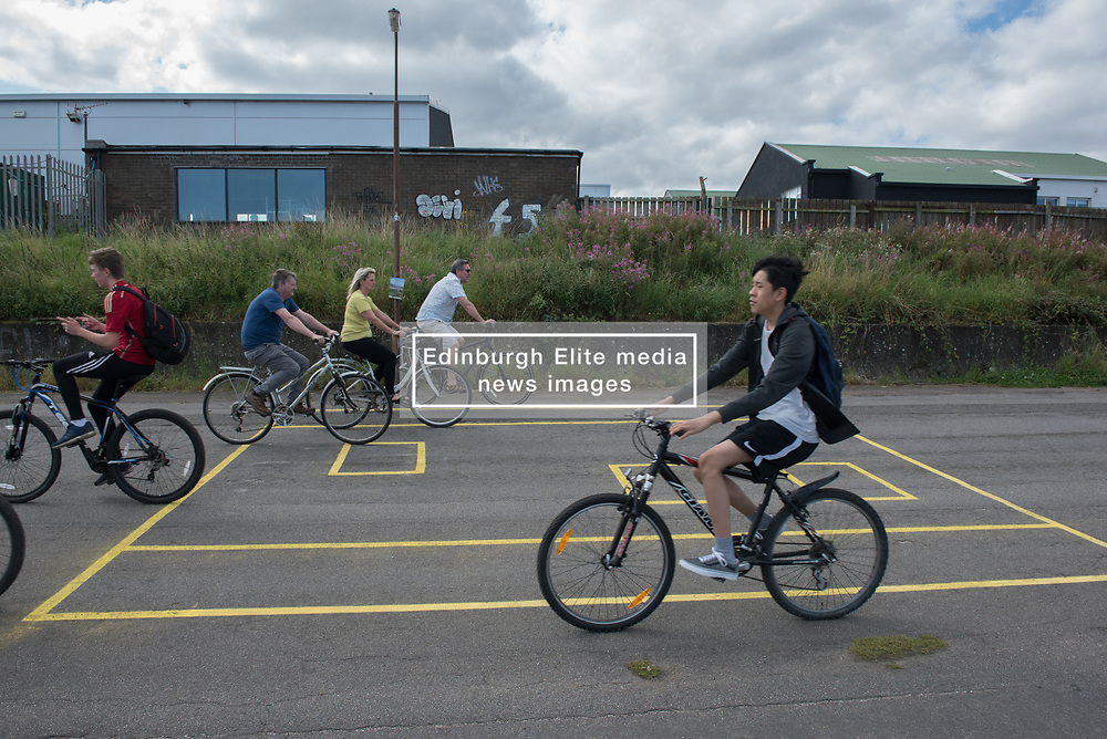 Portobello, Edinburgh's seaside suburb, is awash with Art. Almost everywhere you look there is something to see as the Art Walk Porty community art festival takes place, now extended to run over ten days covering the first two weekends of September. Pictured: Cyclists cross one ofDierdre Macleod's 'Playing Up' drawings.<br /> <br /> <br /> © Jon Davey/ EEm