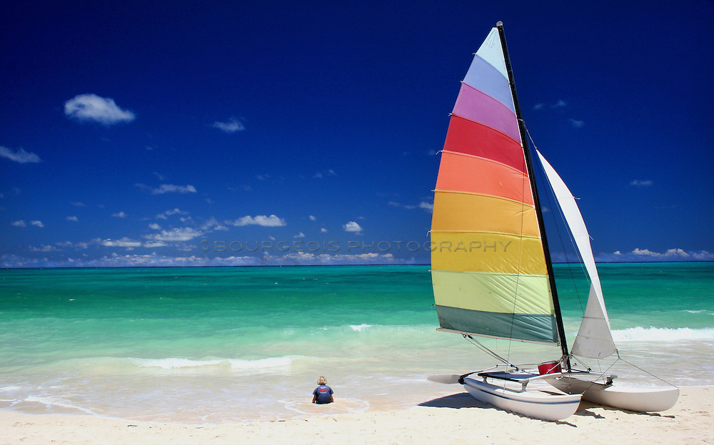 Beach boy and his sailboat amidst the colorful sky and ocean.
