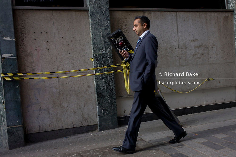 A businessman walks past a leaning automatic traffic control bollard in St . Swithins Lane, City of London.