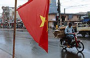 February 2005 - Pleiku, Vietnam - All along the streets of Pleiku, Vietnamese flags hang in commemoration of 60 years since the creation of the Popular Army which was established in 1944. The South Vietnamese Army completely destroyed Pleiku in 1975 as the North Vietnamese Army approached, determined not to give them anything. Hundreds of thousands of people fled into the countryside. In the 1980's with Russian aid, Pleiku was completely re-built and the fleeing people returned. It now has a population of 200,000 people and is set to grow as its location on the 'New' Ho Chi Minh Highway improves its accessibility. Photo Credit: Luke Duggleby