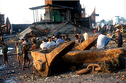 BANGLADESH CHITTAGONG MADHOM BIBIR HAT OCT00 - Labourers stand next to heavy anchor on the ship-breaking beaches of Chittagong. The smoothness of the mud indicates that a large piece of scap metal has been winched across it not too long ago...Several thousand labourers work on one medium-sized (50,000 ton) ship for a period of around three months, until it is completely dismantled and taken apart. ..Since Bangladesh does not possess mineral resources such as iron ore, it works out more cost-efficient to employ a large army of day-labourers to recycle the scrapped ships rather than to import ore. On average, a labourer can expect to earn a little more than 1 US Dollar per day...jre/Photo by Jiri Rezac..© Jiri Rezac 2000..Contact: +44 (0) 7050 110 417.Mobile: +44 (0) 7801 337 683.Office: +44 (0) 20 8968 9635..Email: jiri@jirirezac.com.Web: www.jirirezac.com..© All images Jiri Rezac 2000 - All rights reserved.