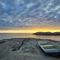 Tranquil Maine at its best showing a dinghy in the foreground leading the way into this Maine seascape scenery of Cape Neddick. Photo was captured at sunrise in York, Maine. I enjoyed this sea view and loved watching this sunrise burst into colors and capturing the boat on the rocks with the beautiful sky and twirling Atlantic Ocean. <br />