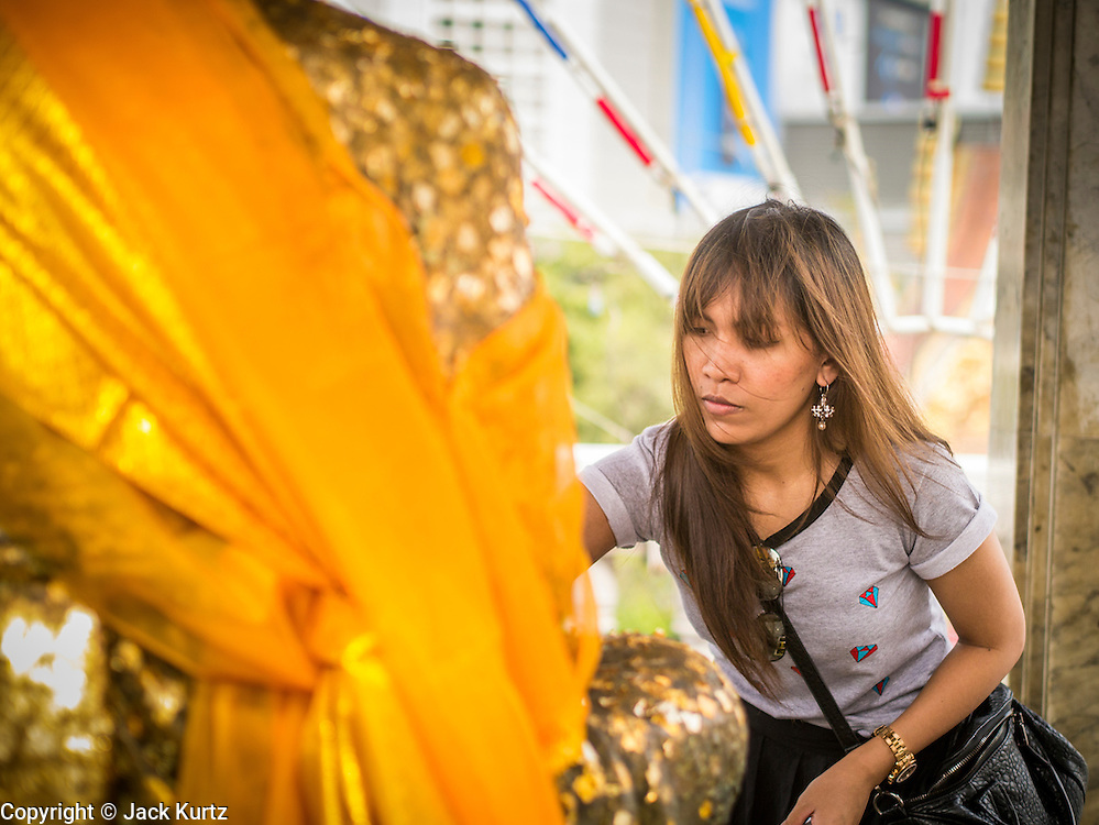 24 FEBRUARY 2013 - BANGKOK, THAILAND: A woman makes merit by applying gold leaf to a statue commemorating a revered monk at Wat Hua Lamphong. Wat Hua Lamphong is a Royal Buddhist temple, third class, in the Bang Rak District of Bangkok, Thailand. It is located on Rama IV Road, approximately 1km from the city's main Hua Lamphong railway station. An entrance to Sam Yan Station on the Bangkok metro (subway) is located outside the main entrance to the temple compound on Rama IV. Wat Hua Lamphong was renovated in 1996 to mark the 50th anniversary of the ascension to the throne of King Bhumibol Adulyadej (Rama IX) in 1996. The royal seal of what became known as the Kanchanapisek, or Golden Jubilee, year, showing two elephants flanking a multi-tiered umbrella, are featured in the temple's remodeling.     PHOTO BY JACK KURTZ
