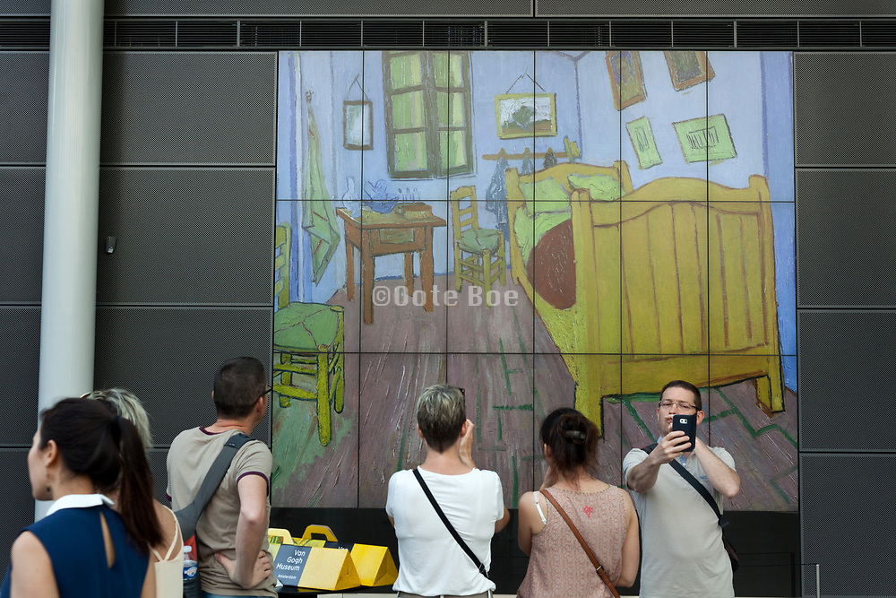 tourists photographing a large screen projection with painting by Van Gogh