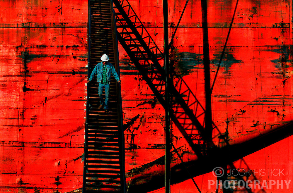 """Mark Ellison, a subcontractor working at Gulf Marine Repair Corp. descends a long staircase leading off of the coal barge """"Pearle Jahn"""" which is dry-docked for repairs at the Port of Tampa, in Tampa, Florida."""