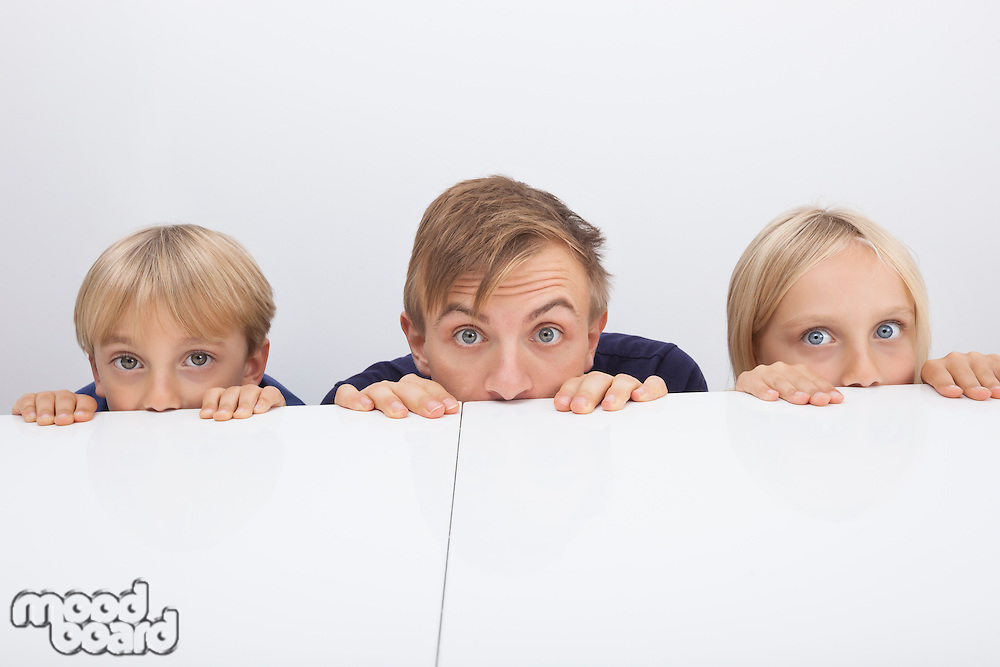 Father and children peeking over table