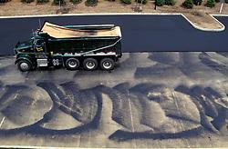 Construction site asphalt paving truck. apartment office complex parking lot. Industrial workplace