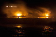 Huge storm waves crash over Penzance Harbour wall at night, backlit by the high pressure sodium floodlights