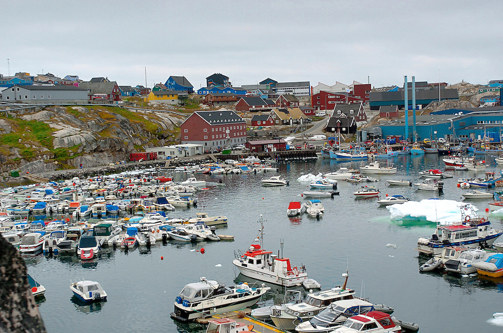 """View of the harbor of Ilulissat, the third largest settlement in Greenland with population 4533, Greenland. Greenland (Greenlandic: Kalaallit Nunaat, meaning """"Land of the Kalaallit (Greenlanders) is a self-governing Danish province located between the Arctic and Atlantic Ocean. A recent study by researchers from NASA's Goddard Space Flight Center shows that Greenland's ice sheet, about 8% of the Earth's grounded ice, is losing ice mass."""