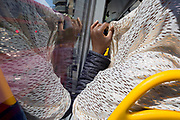 A Muslim lady with her head covered shields her face from strong sunlight on a south London bus, on 14th May, in London, England.