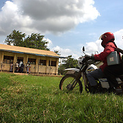 Data clerk Oscar Kai (blue shirt), arrives at the Ngamani Primary School for an outreach clinic with his laptop and shoulder carried cooler of vaccines. Mothers in colorful shawls with babies on their backs arrive holding purple booklets given out by the government, that until the GAVI funded PCV Impact study, were families only records of health. <br /> <br /> Alongside the PCV10 vaccine, records are kept of pentavalent, BCG, polio, yellow fever, measles, diphtheria, tetanus and hepatitis B immunizations. All of that fresh information is uploaded to portable hard-drives  that are weekly to the study headquarters, where the database is updated.<br /> <br /> &quot;Because the database is digitized, it means it's far easier to keep our records fresh, even if children move and access health services in different locations,&quot; says Dr.Benjamin Tsofa, the Kenyan health ministry's chief liaison on the study. <br /> <br /> In January 2011, the Kenyan government with support from the GAVI Alliance, introduced a new vaccine, PCV-10, which targets 10 bacteria than can cause Invasive Pneumococcal Disease.The vaccine's impact is monitored through an electronic database, part of the GAVI funded PCV impact study, which maps the growing coverage of the new vaccine. Already, here in Kilifi, the incidence of the illness in children aged five has gone down by approximately two-thirds.