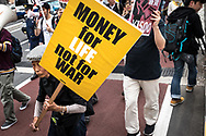 Protesters carrying signs demanding a higher wage Tokyo April 15, 2017, Japan. A Group of young people named Aequitas who means Equity in Latin, organised a demonstration to demanded a minimum hourly wage of 1,500 JPY (approx. USD 13.7), currently the minimum wage ranges from 700 to 900 JPY (approx. USD from 6,4 to 8,3). 15/04/2017-Tokyo, JAPAN