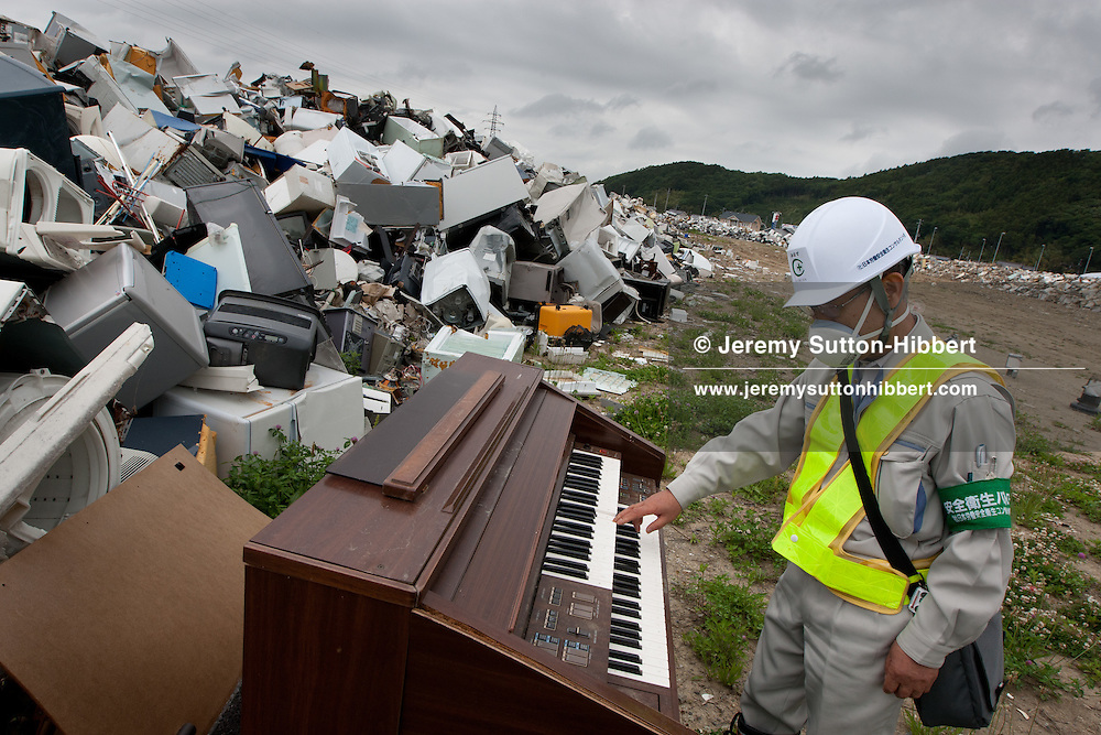 Mamoru Minase, a worker with 'JASHCON' (a labour workers environmental health inspector) examines the waste, debris and refuse from the destruction caused by the March 11th earthquake and tsunami which has been brought to prefectural-owned land to be stored/dumped, and which sits beside the Senior High School of Commerce, in Ishinomaki, Tohoku region, Japan, on Friday 17th June 2011. There are now fears for the pollution and health risks that this debris now holds, including the releasing into the air of asbestos dust.