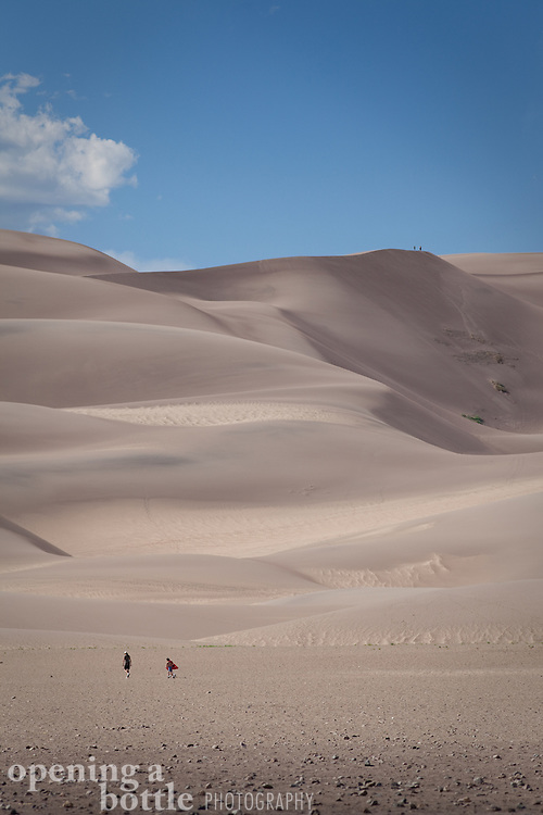 People are dwarfed by the towering dunes of the dune field, at Great Sand Dunes National Park, Colorado.