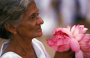 Woman at a Buddhist temple with an offering of flowers.
