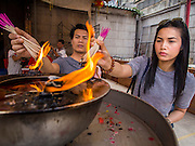 "17 FEBRUARY 2015 - BANGKOK, THAILAND:  People light candles and incense for Chinese New Year at Wat Mangkon Kamalawat, the largest and most important Chinese Buddhist temple in Bangkok. Chinese New Year is February 19 in 2015. It marks the beginning of the Year of Sheep. The Sheep is the eighth sign in Chinese astrology and the number ""8"" is considered to be a very lucky number. It symbolizes wisdom, fortune and prosperity. Ethnic Chinese make up nearly 15% of the Thai population. Chinese New Year (also called Tet or Lunar New Year) is widely celebrated in Thailand, especially in urban areas like Bangkok, Chiang Mai and Hat Yai that have large Chinese populations.      PHOTO BY JACK KURTZ"