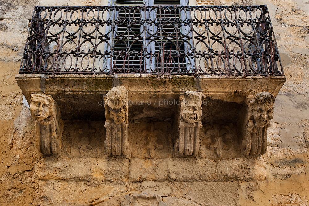 Naro, Italia - il 16 September 2012: Decorazioni grottesche di un balcone di palazzo Gaetani a Naro, Italia, il 16 September 2012. Spesso i prospetti degli edifici civili di Naro sono adorni di mascheroni e volute intensamente chiaroscurati.