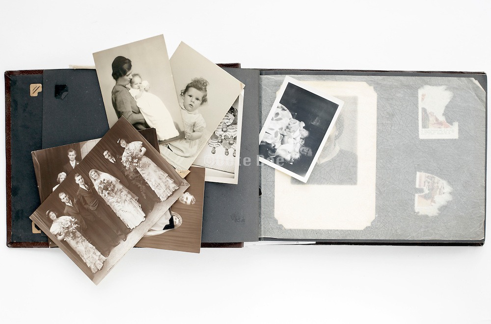 family photo album with loose images from 1920s and 1950s
