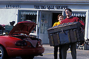 Happy young couple with an antique treasure chest trying to fit it in their sports car.