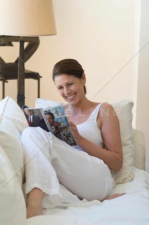 Woman enjoying reading a magzine relaxed on a white sofa