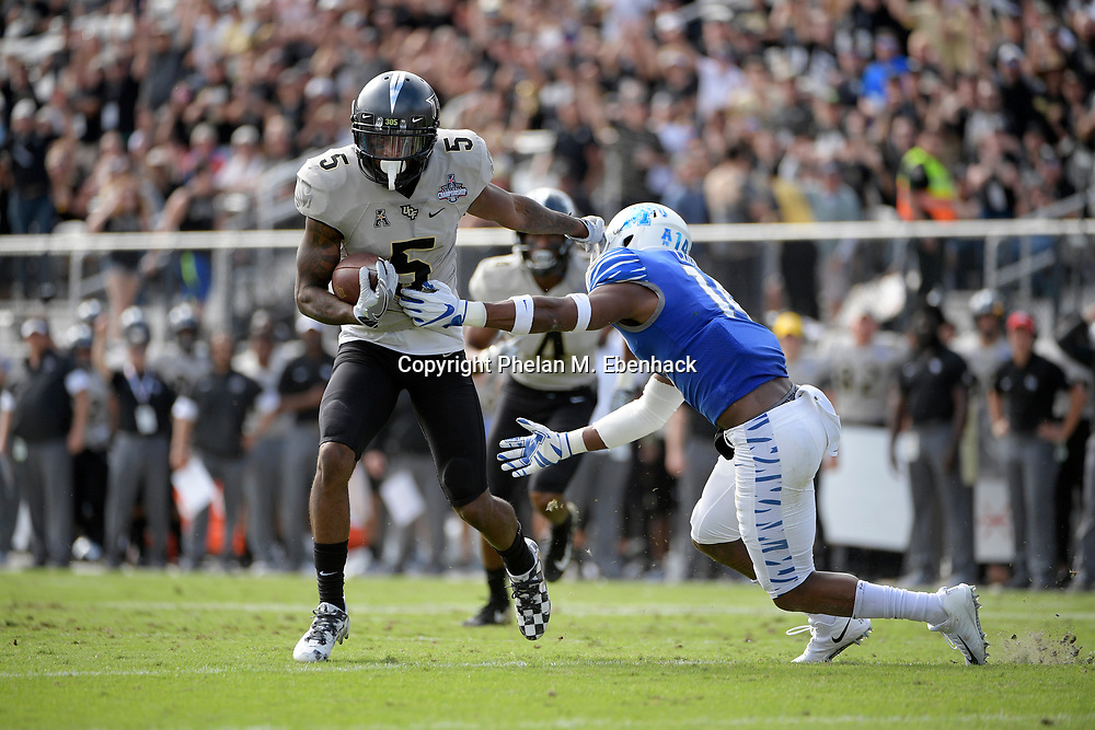 Central Florida wide receiver Dredrick Snelson (5) runs into the end zone for a touchdown in front of Memphis defensive back Jonathan Cook (14) after catching a pass during the first half of the American Athletic Conference championship NCAA college football game Saturday, Dec. 2, 2017, in Orlando, Fla. (Photo by Phelan M. Ebenhack)