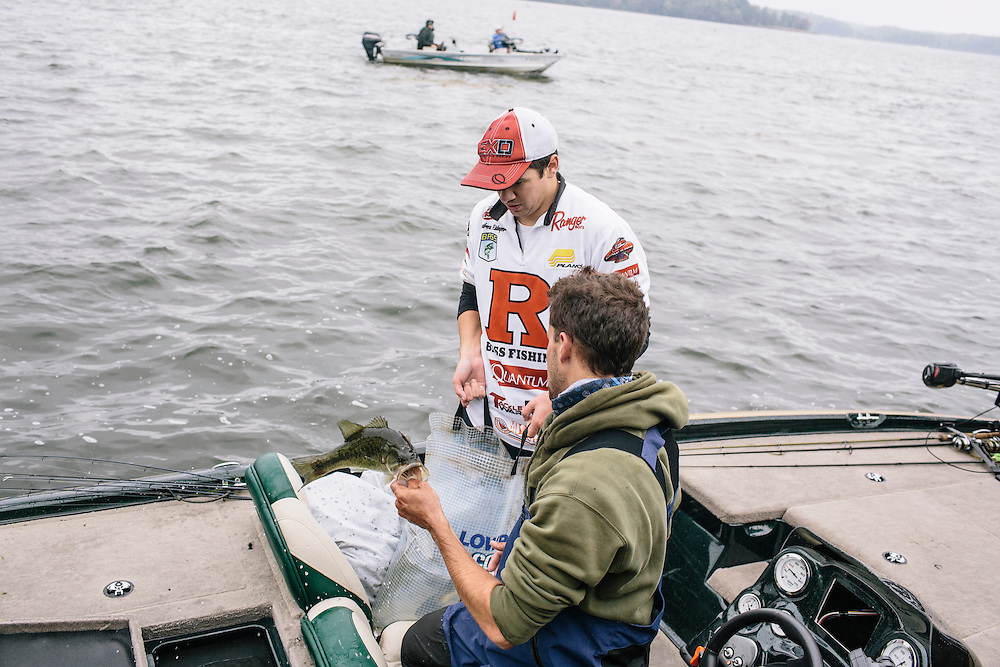 Andrew Ridinger, left, and Kyle Genova, right, of Rutgers University, put their bass into a bag to be weighed during the FLW College Fishing Northern Conference Invitational in Marbury, MD on Oct. 11, 2014. Only the top 15 of 43 teams moved on to Sunday.