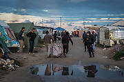 CALAIS, FRANCE - OCT 22: Refugees are seen carrying their belongings inside the 'jungle' camp in Calais, France on October 22, 2016.