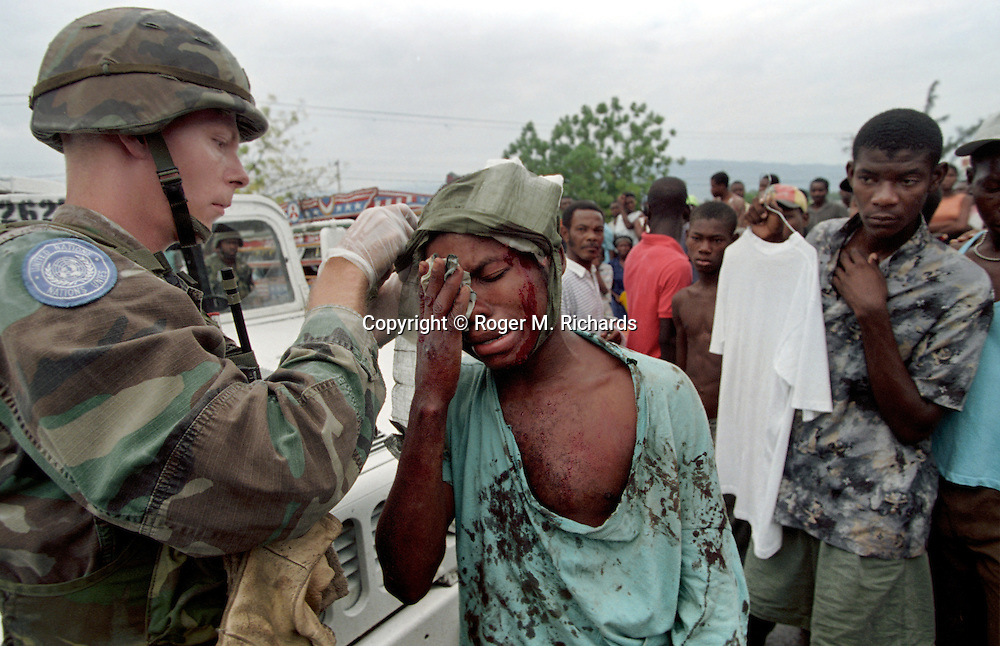 A US soldier aids a civilian wounded in a street fight, Haiti, May 1995. (Photo by Roger M. Richards)
