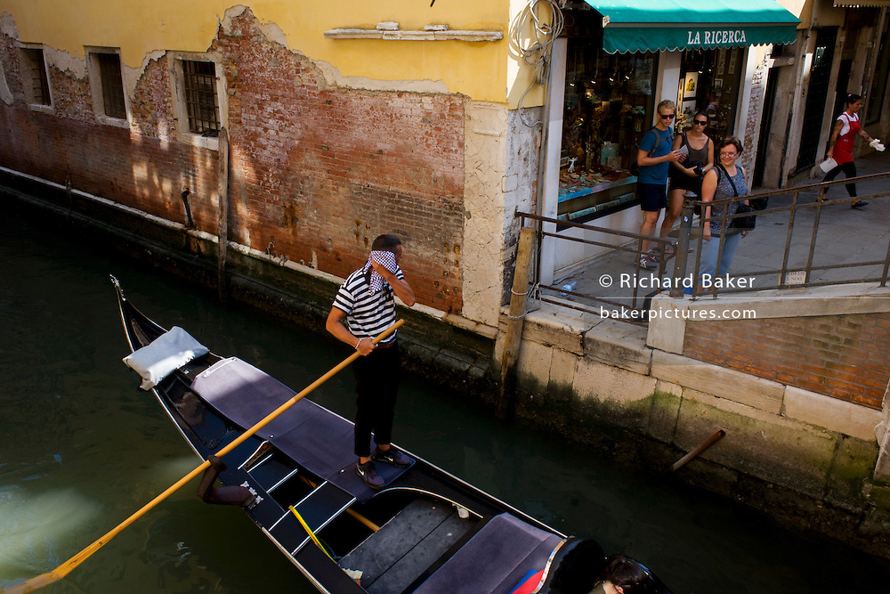 Hot gondolier wipes his brow during a heatwave, to the amusement of tourists, in Venice, Italy. Current prices (2015) is 80 Euros for a 40-minute journey (earning them approx 130,000 Euros a year) along the waterways of this old city but rarely do gondoliers wear their straw hat.