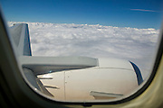 A Boeing 737 jetliner flies over a solid cloud bank in this view from a passenger window.