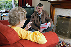 Welfare rights worker and Service Users discussing a form during a home visit,