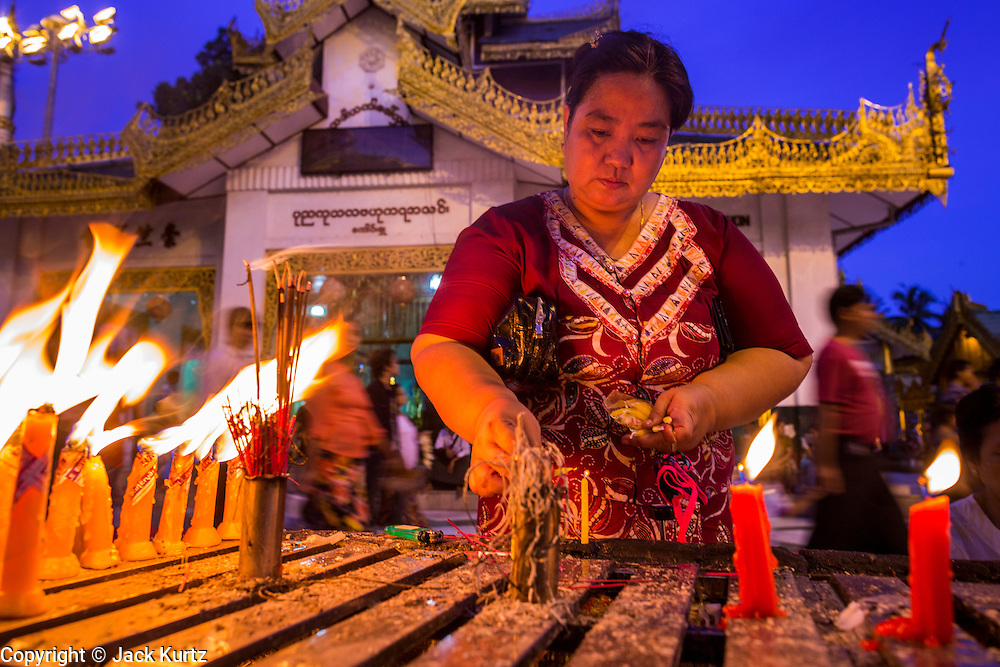 15 JUNE 2013 - YANGON, MYANMAR: A woman makes merit and prays with candles at Shwedagon Pagoda. The Shwedagon Pagoda is officially known as Shwedagon Zedi Daw and is also called the Great Dagon Pagoda or the Golden Pagoda. It is a 99 metres (325ft) tall pagoda and stupa located in Yangon, Burma. The pagoda lies to the west of on Singuttara Hill, and dominates the skyline of the city. It is the most sacred Buddhist pagoda in Myanmar and contains relics of the past four Buddhas enshrined: the staff of Kakusandha, the water filter of Koṇāgamana, a piece of the robe of Kassapa and eight strands of hair fromGautama, the historical Buddha. The pagoda was built between the 6th and 10th centuries by the Mon people, who used to dominate the area around what is now Yangon (Rangoon). The pagoda has been renovated numerous times through the centuries. Millions of Burmese and tens of thousands of tourists visit the pagoda every year, which is the most visited site in Yangon.    PHOTO BY JACK KURTZ