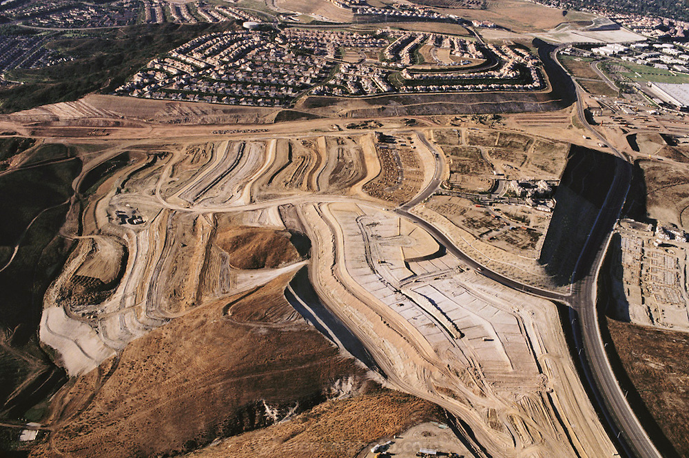 San Joaquin corridor toll road grading near Laguna beach in Orange County, California. Aerial shows massive earth grading for roads and homes; leveling hills to make plateaus and benches for subdivisions.