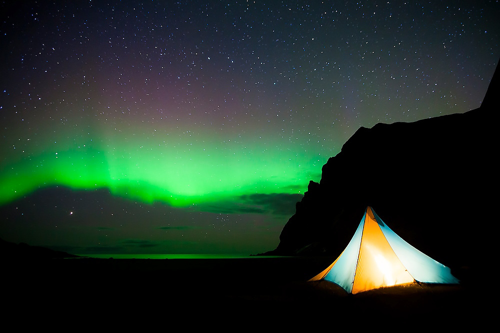 The aurora borealis appears above a glowing tent on Bunes Beach, Moskenesoya, Lofoten Islands, Norway.