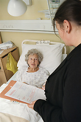 Elderly woman lying in hospital bed on ENT ward talking to Operational services manager,