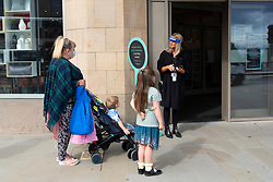 Edinburgh, Scotland, UK. 13 July, 2020, Monday in Scotland saw re-opening of shopping centres after further relaxation of coronavirus lockdown on business. John Lewis & Partners department store opened early at 9.30 am after a long queue had formed outside. Pictured; mother with children were at the head of the queue and first to go inside. Iain Masterton/Alamy Live News