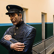 A life-sized model of a prison guard looking down over the cell blocks at the Maritime Museum of Ushuaia. The museum consists of several wings devoted to maritime history, Antarctic exploration, an art gallery, and a policy and penitentiary museum. The complex is housed in an historic prison building and uses the original cells and offices as exhibit spaces.