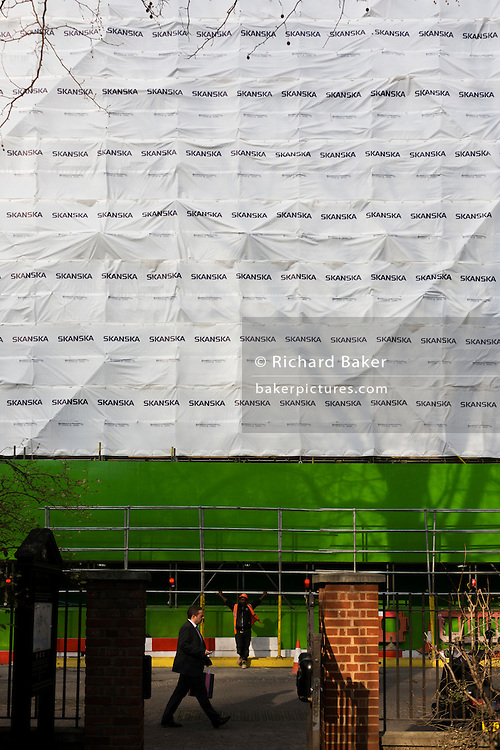 Construction workman below safety sheeting with plain tree shadow at a Skanska building project in Finsbury Circus.