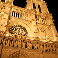 Facade of the Notre Dame Cathedral in Paris at night.