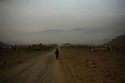 A migrant woman walks away from a land invasion in the outskirts of Lima, Peru, Wednesday, March, 18, 2009. Land invasions from Indigenous communities from the Peruvian highlands, more and more common after the 70's, increase the pressure on the water resources of an 8 million capital that has already been built in the slopes of sandy, desertic mountains and extremely dependent on the glaciers for its supply.