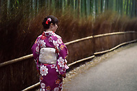 Japanese woman in a purple kimino walking through Arashiyama bamboo forest in Kyoto, Japan.