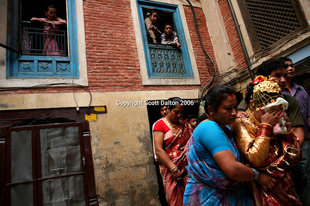 A new bride cries as she is escorted by family members after a traditional wedding ceremony in Patan on June 8, 2006. (Photo/Scott Dalton)