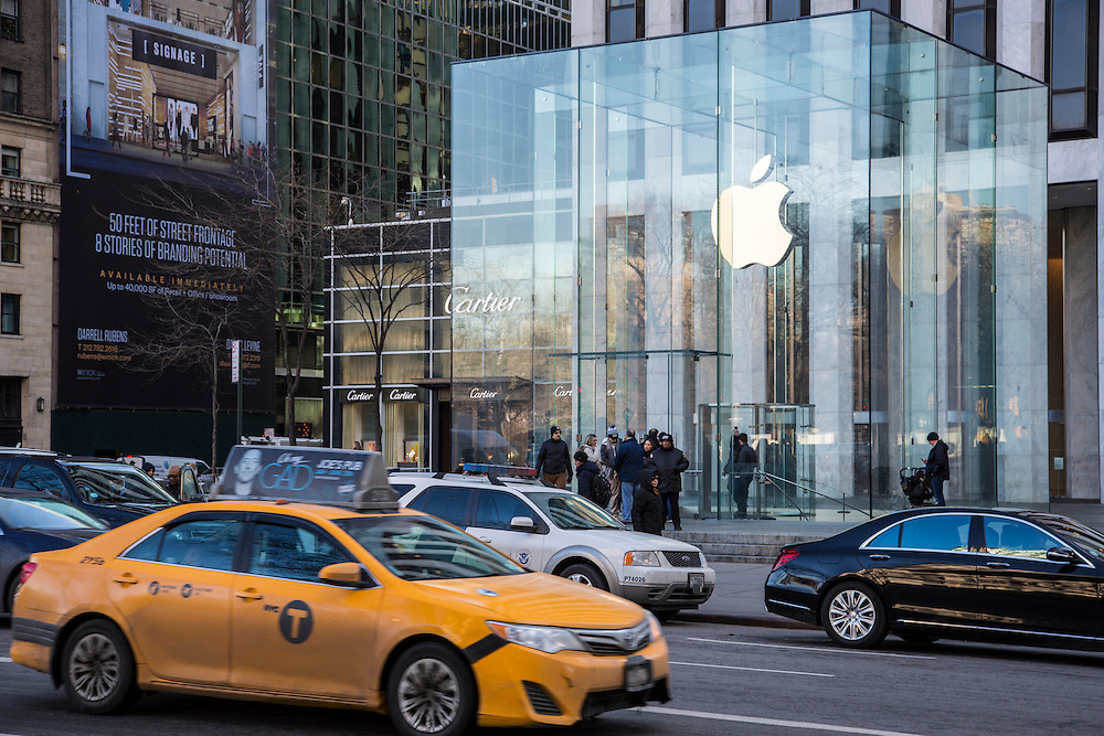 An iconic New York yellow taxi and other cars drive past Apple Inc's flagship Apple Store on 5th Avenue, New York City, New York, United States of America.  (photo by Andrew Aitchison / In pictures via Getty Images)