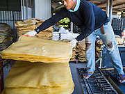 "15 DECEMBER 2014 - CHUM SAENG, RAYONG, THAILAND: A farmer unloads rubber sheets from his truck at a rubber buying station in Chum Saeng, Thailand. Thailand is the second leading rubber exporter in the world. In the last two years, the price paid to rubber farmers has plunged from approximately 190 Baht per kilo (about $6.10 US) to 45 Baht per kilo (about $1.20 US). It costs about 65 Baht per kilo to produce rubber ($2.05 US). Prices have plunged 5 percent since September, when rubber was about 52Baht per kilo. Some rubber farmers have taken jobs in the construction trade or in Bangkok to provide for their families during the slump. The Thai government recently announced a ""Rubber Fund"" to assist small farm owners but said prices won't rebound until production is cut and world demand for rubber picks up.     PHOTO BY JACK KURTZ"