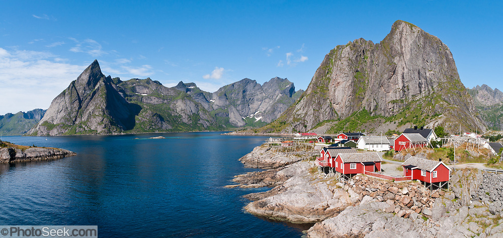 Red rorbus perch on stilts in Hamnøy  fishing village along the shore of Reinefjord, Lofoten archipelago, Nordland county, Norway. Panorama stitched from 2 overlapping photos.