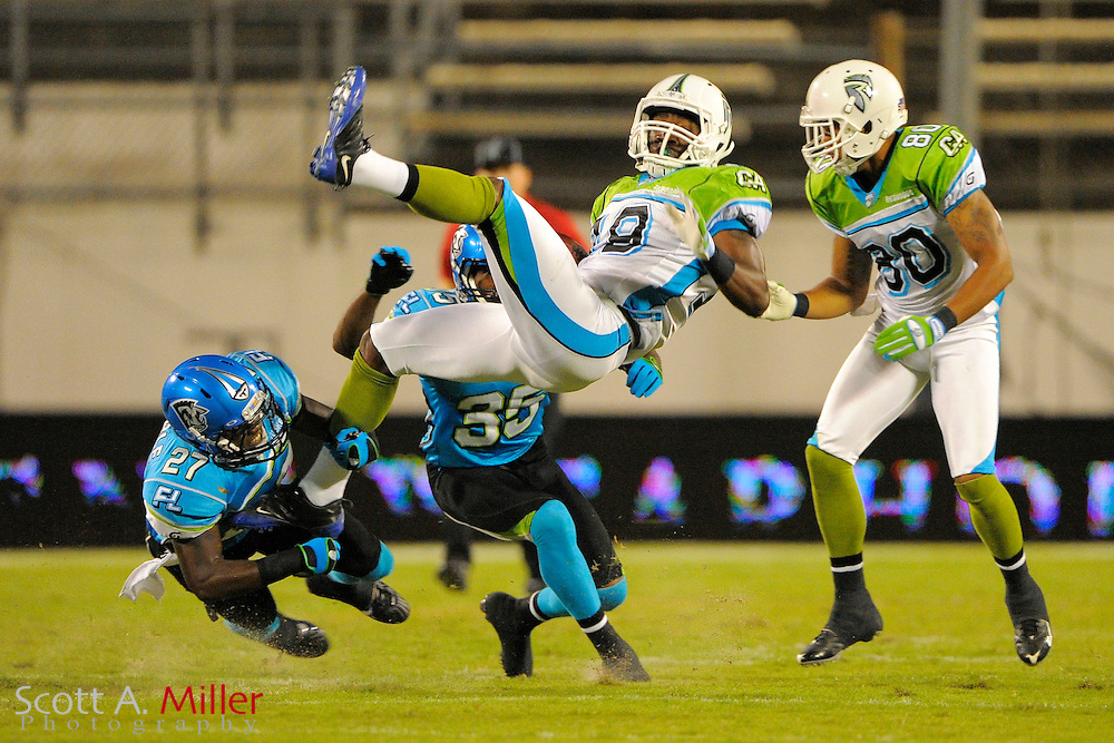 Orlando, Florida ; Oct 22, 2009: California Redwoods wide receiver Joe West (19) is flipped after making a reception by Florida Tuskers cornerback Fakhir Brown (35) and defensive back DeJuan Tribble (27) during the first half at the Citrus Bowl. .