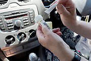 A middle-aged lady attatches her personal barcode to the plastic vial after testing herself while sitting in the driver's seat of her car during a self-administered Coronavirus (COVID-19) test in south London. There are four steps to the self-administered Covid-19 test (inserting a swab into the nose and throat) which the public works through in their car, windows up and all communications with army personnel via phone, in a south London leisure centre, on 2nd June 2020, in London, England. The kit provided consists of a booklet, plastic bag, swab, vial, bar codes and a sealable biohazard bag. The swab sample is taken from the back of the throat and nasal passage with the contents sealed and returned to soldiers through a narrow window. The whole process takes between 5-10mins with results available with 48hrs.
