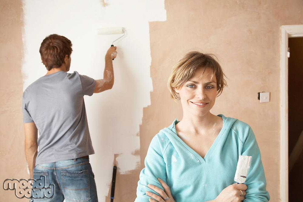 Woman holding paint brush next to man painting interior wall