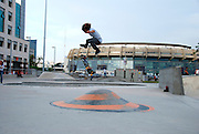 Israel, Tel Aviv, Yad Eliyahu, Urban extreme sport park. Young male performing stunts with a skateboard. The Basketball Stadium in the background